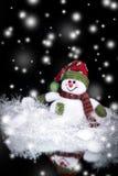 Muñeco de nieve lindo del juguete en un fondo negro Imagenes de archivo