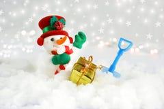 Muñeco de nieve lindo en nieve con la pala y el regalo Foto de archivo