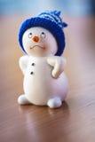 Muñeco de nieve lindo en la tabla de madera Imagenes de archivo