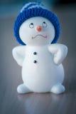 Muñeco de nieve lindo en la tabla de madera Foto de archivo libre de regalías