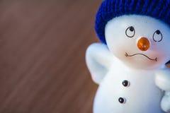 Muñeco de nieve lindo en la tabla de madera Fotos de archivo libres de regalías
