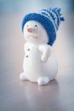 Muñeco de nieve lindo en la tabla de madera Fotos de archivo