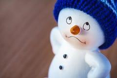 Muñeco de nieve lindo en la tabla de madera Imagen de archivo libre de regalías