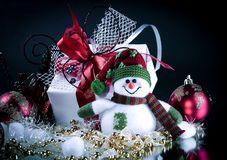 Muñeco de nieve lindo de la caja de juguetes con los regalos en un fondo negro Imagen de archivo