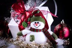 Muñeco de nieve lindo de la caja de juguetes con los regalos en un fondo negro Imagen de archivo libre de regalías