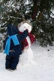 Muñeco de nieve por el árbol de navidad Imágenes de archivo libres de regalías