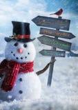 Muñeco de nieve que lleva a cabo la muestra de madera con saludos Foto de archivo libre de regalías