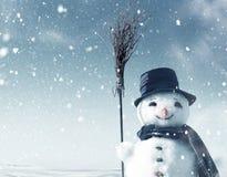 Muñeco de nieve que se coloca en paisaje de la Navidad Imagen de archivo