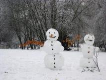 Muñeco de nieve que se coloca en paisaje del invierno Imagen de archivo