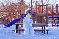 Muñeco de nieve que se sienta en un banco Imagen de archivo