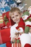 Muñeco de nieve relleno tenencia del muchacho en Front Of Christmas Tree Imagen de archivo