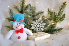 Muñeco de nieve sentido divertido con un regalo en el fondo de las ramas del abeto con las luces de la guirnalda en la nieve en u foto de archivo libre de regalías