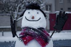 Muñeco de nieve sonriente alegre que se sienta en el banco imagen de archivo libre de regalías