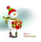 Muñeco de nieve sonriente con el regalo de la Navidad Foto de archivo libre de regalías