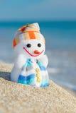 Muñeco de nieve sonriente del juguete en la playa del mar Fotografía de archivo libre de regalías