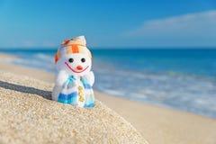 Muñeco de nieve sonriente del juguete en la playa del mar Imagen de archivo
