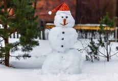 Muñeco de nieve sonriente en un sombrero de Santa Claus Imagen de archivo
