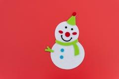 Muñeco de nieve sonriente plano de la Navidad del juguete con la bufanda verde imagen de archivo