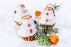 Muñeco de nieve de tres blancos del mazapán y del merengue en la tabla de la Navidad Foco selectivo Imagen de archivo