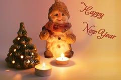 Muñeco de nieve, velas ardientes y árbol de navidad La Navidad foto de archivo libre de regalías