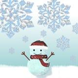 Muñeco de nieve vestido en casquillo y bufanda hechos punto Fotografía de archivo