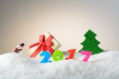 Muñeco de nieve y árbol de la decoración de la Navidad en la nieve Foto de archivo libre de regalías