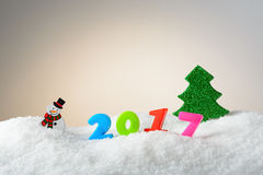 Muñeco de nieve y árbol de la decoración de la Navidad en la nieve Fotografía de archivo