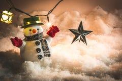 Muñeco de nieve y bombilla en nieve en la noche silenciosa Imagen de archivo