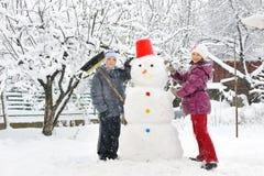 Muñeco de nieve y cabritos Imagenes de archivo