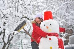 Muñeco de nieve y chica joven fotos de archivo