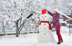Muñeco de nieve y chica joven Fotos de archivo libres de regalías