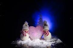 Muñeco de nieve y mujer de la nieve con el corazón en nieve en fondo oscuro Imagen conceptual del Año Nuevo y de la Navidad con e Fotos de archivo