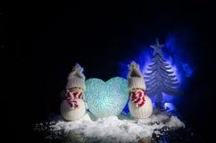Muñeco de nieve y mujer de la nieve con el corazón en nieve en fondo oscuro Imagen conceptual del Año Nuevo y de la Navidad con e Imagen de archivo