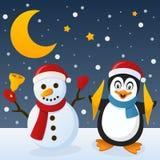 Muñeco de nieve y pingüino en la nieve Imagen de archivo