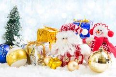 Muñeco de nieve y Santa Claus del juguete de la Navidad en fondo nevoso Imagen de archivo