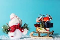 Muñeco de nieve y trineo con los regalos de la Navidad en fondo ciánico foto de archivo libre de regalías