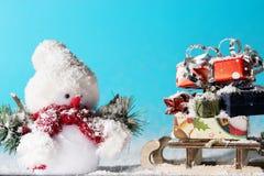 Muñeco de nieve y trineo con los regalos de la Navidad en fondo ciánico imagen de archivo libre de regalías