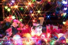 Muñeco de nieve y un árbol de navidad adornado con la luz Imagenes de archivo