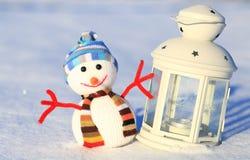 Muñeco de nieve y velas decorativas en nieve Fotos de archivo libres de regalías