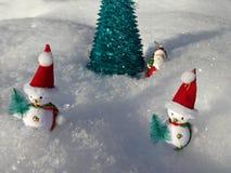 Muñecos de nieve cerca del árbol de navidad artificial en la nieve Imágenes de archivo libres de regalías