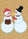 Muñecos de nieve debajo de la nieve que cae Imagenes de archivo
