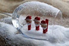 Muñecos de nieve de la Navidad en pinzas, dentro de un cubilete de cristal Fotografía de archivo libre de regalías