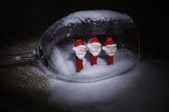 Muñecos de nieve de la Navidad en pinzas, dentro de un cubilete de cristal Imagen de archivo libre de regalías