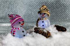 Muñecos de nieve plásticos en nieve Fotos de archivo libres de regalías