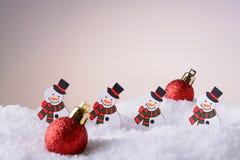 Muñecos de nieve y bolas del ornamento de la Navidad en la nieve Fotos de archivo libres de regalías