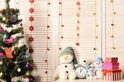 Muñecos de nieve y osos de peluche cerca del reloj y del árbol de navidad imagen de archivo libre de regalías
