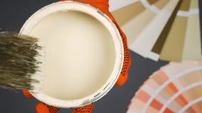 Muśnięcie i otwiera może z beżową farbą nad szarym tłem Palet lekcy colours zdjęcie wideo