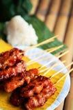 `-Mu knackar ` grillad grisköttThailand stil som tjänas som med klibbiga ris på bananbladet Arkivbild