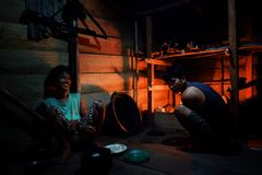 Liki and an other tribal boy is preparing the dinner in their jungle ho stock photography