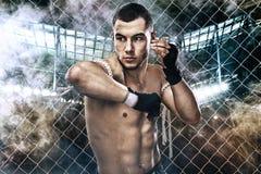 Muay ταϊλανδική πάλη μπόξερ αθλητικών τύπων στον εγκιβωτισμό του κλουβιού Υπόβαθρο με τα φω'τα και τον καπνό διάστημα αντιγράφων Στοκ φωτογραφία με δικαίωμα ελεύθερης χρήσης